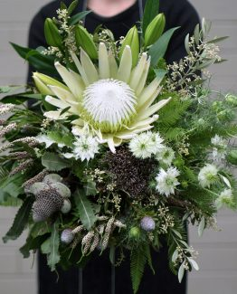 "INDUSTRIAL Bridal Bouquet ""Zoe"" consisting of King protea, oriental lilies, native flowers, foliage and fern. Image by The White Orchid Floral Design."