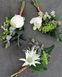 INDUSTRIAL Buttonholes consisting of ranunculi (top left), freesia (top right) and paper daisy (bottom) all framed with textured foliage and fern, finished with copper wire.  Image by The White Orchid Floral Design.