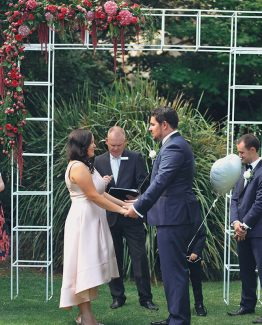 INDUSTRIAL Ceremony Floral Arch Corner Spray consisting of hydrangea, roses, celosia, amaranthus and pepper berry.  Image by Evan Bailey Photography.