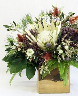 INDUSTRIAL Gold Pot Arrangement consisting of King protea, native flowers, foliages and ferns.  Image by The White Orchid Floral Design.