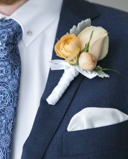 ROMANTIC Buttonhole consisting of a rose with ranunculi buds framed with dusty miller, finished with satin ribbon.  Image by Alice Healy Photography.