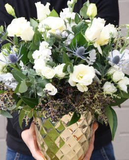 INDUSTRIAL Gold Pot Arrangement consisting of white lisianthus, stocks, roses, spray roses, blue sea holly, blue gum  foliage and ferns.  Image by The White Orchid Floral Design.