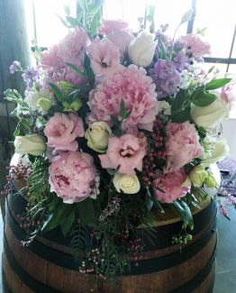 GARDEN Wine Barrel Arrangement consisting of peonies, roses, lisianthus, stocks and pepper berry. Image by The White Orchid Floral Design.
