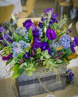 GARDEN Wooden Box Arrangement consisting of lisianthus, hydrangea, succulents, lavender, sea holly, hebe and magnolia leaf.  Image by Panache Photography.